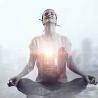 Exposure image of young meditating woman and modern cityscape
